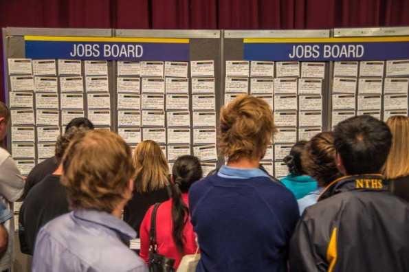 Job seekers checking the jobs board at an employment expo in Hobart (c) Rob Walls 2013