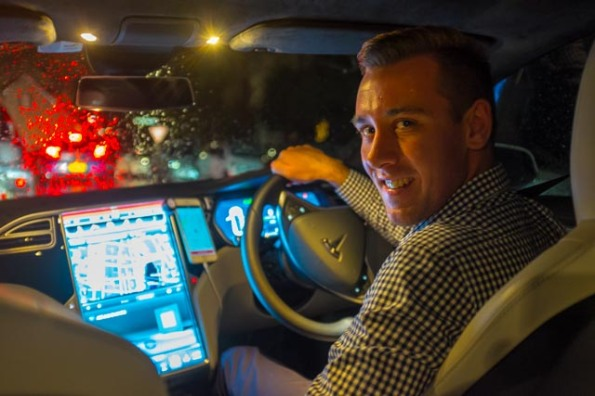 New technology takes over the taxi industry. Student viticulturist and Uber driver, Justin Gibbons at the wheel of a new Tesla electric vehicle in Sydney. © Rob Walls 2015